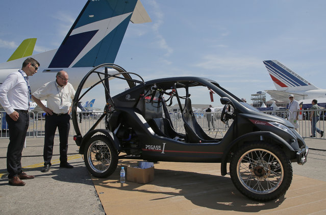 Visitors looks at the flying car Pegasus 1, built by French entrepreneur Jerome Dauffy at Paris Air Show, in Le Bourget, east of Paris, France, Tuesday, June 20, 2017. Aviation professionals and spectators are expected at this week's Paris Air Show, coming in, in a thousands from around the world to make business deals. (Photo by Michel Euler/AP Photo)