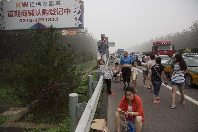Travellers react as the highway from Beijing to China's Hebei Province is reopened, after in was closed due to low visibility on a heavy polluted morning August 3, 2015. (Photo by Damir Sagolj/Reuters)
