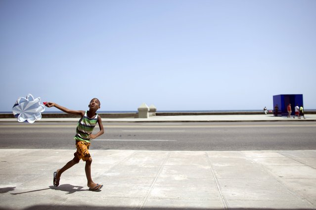 A boy plays with a parachute at the sea front Malecon in Havana, July 7, 2015. (Photo by Alexandre Meneghini/Reuters)
