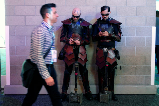 A man walks past two video game characters checking their cell phones at the E3 Electronic Expo in Los Angeles, California, U.S. June 14, 2016. (Photo by Lucy Nicholson/Reuters)