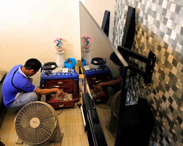 A agent of the National Bureau of Investigation searches for evidence during a raid at the home of a police officer and member of the drugs unit, in metro Manila, Philippines May 25, 2016. (Photo by Romeo Ranoco/Reuters)