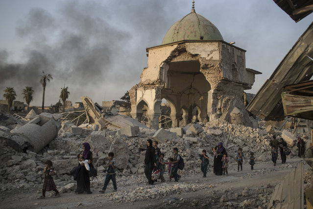 Fleeing Iraqi civilians walk past the heavily damaged al-Nuri mosque as Iraqi forces continue their advance against Islamic State militants in the Old City of Mosul, Iraq, Tuesday, July 4, 2017. As Iraqi forces continued to advance on the last few hundred square kilometers of Mosul held by the Islamic State group, the country's Prime Minister said Tuesday the gains show Iraqis reject terrorism. (Photo by Felipe Dana/AP Photo)