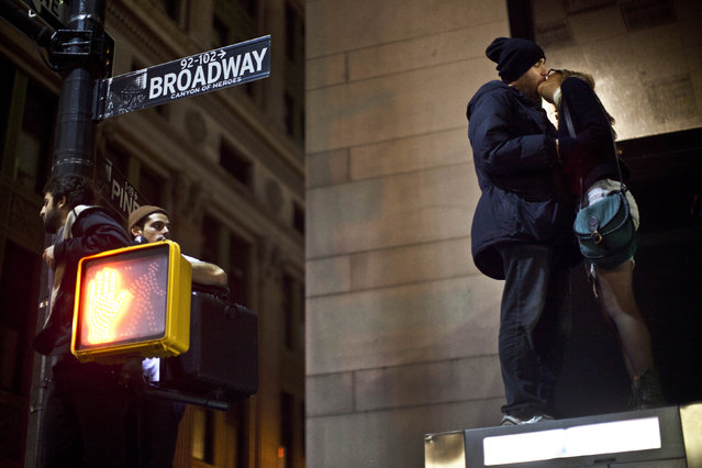 Protesters affiliated with the Occupy Wall Street movement kiss while standing on top of a bus stop during an unannounced raid by the New York City Police Department outside Zuccotti Park in New York, in the early hours of November 15, 2011. (Photo by Andrew Burton/Reuters)