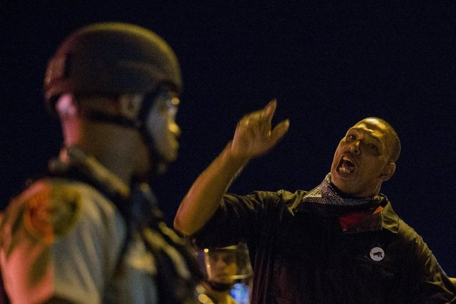 An anti-police demonstrators screams at a St Louis County police officers during protests in Ferguson, Missouri August 11, 2015. (Photo by Lucas Jackson/Reuters)