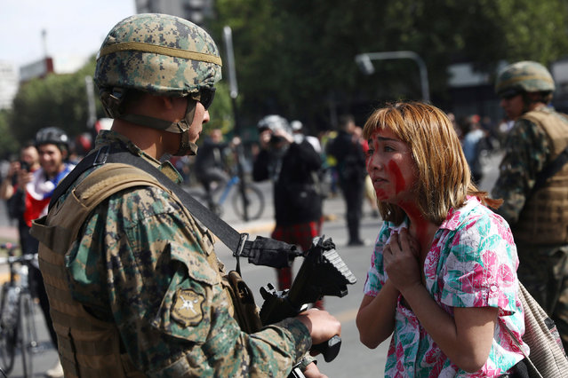 A demonstrator gestures in front of a soldier during a protest against the increase in subway ticket prices in Santiago, Chile, October 19, 2019. (Photo by Edgard Garrido/Reuters)
