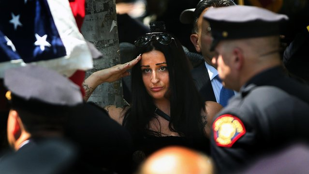 People watch as the flag-draped coffin of slain Jersey City police officer Melvin Santiago, 23, passes by following a funeral mass in Jersey City, New Jersey, on Jule 18, 2014. Police from the New Jersey and New York area took part in a procession for Santiago, who was shot and killed in the line of duty during an armed robbery. (Photo by John Moore/Getty Images)