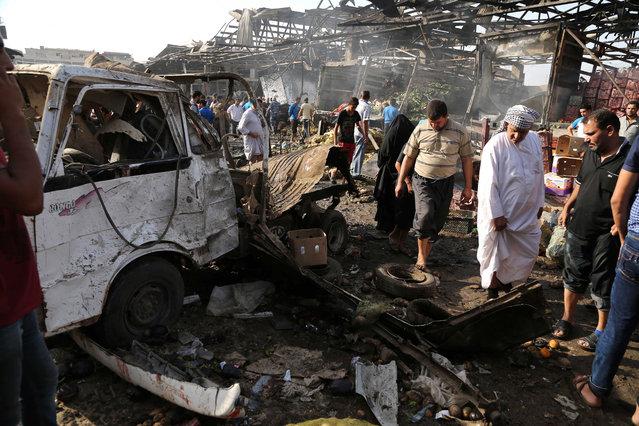 Civilians inspect the scene of bomb attack in Jameela market in the Iraqi capital's crowded Sadr City neighborhood Baghdad, Iraq, Thursday, August 13, 2015. (Photo by Karim Kadim/AP Photo)
