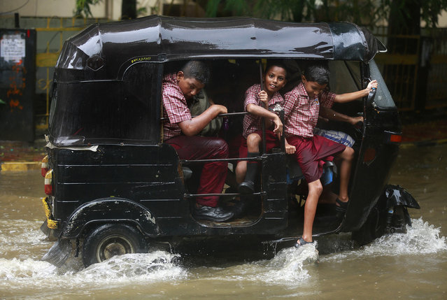 School children ride an auto rickshaw through a flooded street as it rains in Mumbai, India, Tuesday, June 28, 2016 . Monsoon rains, which started off slow in the city, has picked up pace the past few days. India's monsoon season runs from June to September. (Photo by Rafiq Maqbool/AP Photo)
