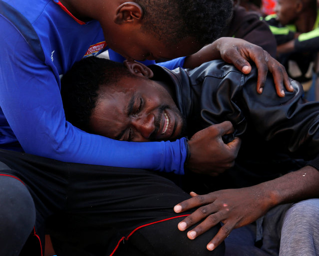 A migrant is comforted by a friend after being rescued, on the Migrant Offshore Aid Station (MOAS) ship Topaz Responder, around 20 nautical miles off the coast of Libya, June 23, 2016. (Photo by Darrin Zammit Lupi/Reuters)