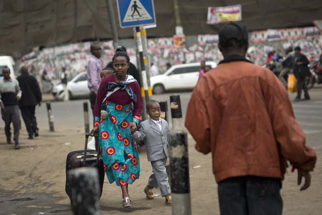 A Kenyan woman and her child walk towards the bus station in Nairobi, Kenya, Monday August 7, 2017. (Photo by Jerome Delay/AP Photo)
