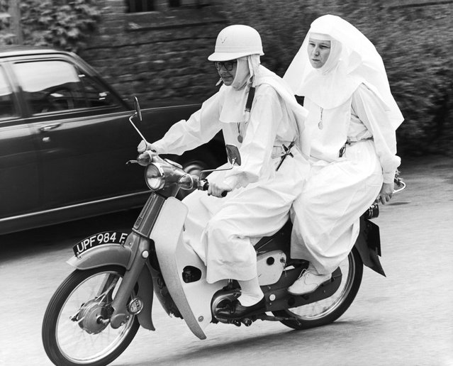 English nun Sister Joan Capistran taking Sister Mary Grace for a pillion ride on her 50cc Honda moped in the grounds of Ladywell Convent, Godalming, Surrey, 11th July 1969