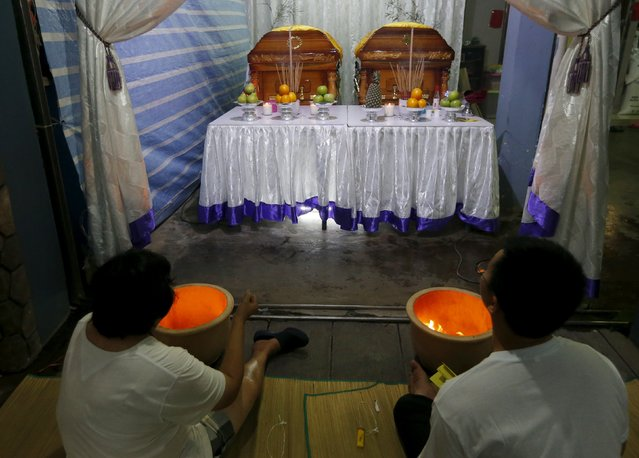 Family members of Neoh Hock Guan, a survivor of Monday's blast in Bangkok, pay their last respects to his wife and son who were killed in the attack in Butterworth, Malaysia, August 20, 2015. (Photo by Olivia Harris/Reuters)