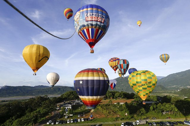 Spectators view hot air balloon during the 2016 International Hot Air Balloon Festival in Taitung, southeast of Taiwan, 01 July 2016. (Photo by Ritchie B. Tongo/EPA)