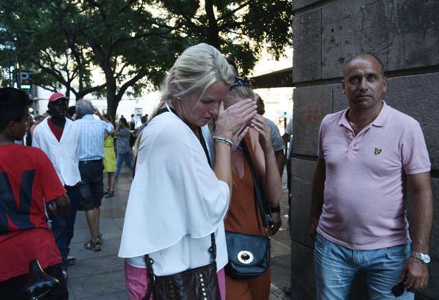 A woman is comforted as crowds flee from the scene after a white van jumped the sidewalk in the historic Las Ramblas district of Barcelona, Spain, crashing into a summer crowd of residents and tourists Thursday, August 17, 2017. According to witnesses the white van swerved from side to side as it plowed into tourists and residents. (Photo by Giannis Papanikos/AP Photo)
