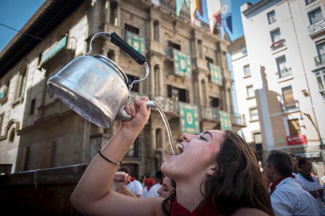 A woman drinks before the Riau-Riau procession of the San Fermin Festival on July 6, 2016 in Pamplona. The Riau-Riau is a procession held on 6 July in which members of the city council parade from the City Hall to a nearby chapel dedicated to Saint Fermin, on July 6, 2016. (Photo by Pedro Armestre/AFP Photo)
