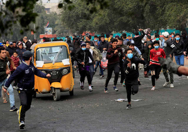 Iraqi demonstrators run away for a cover during ongoing anti-government protests in Baghdad, Iraq on January 29, 2020. (Photo by Thaier al-SudanI/Reuters)
