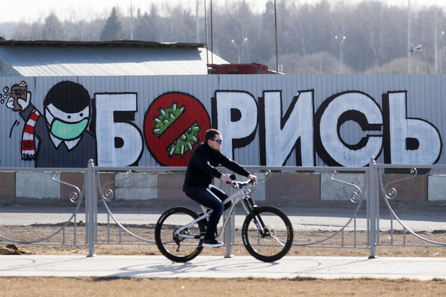 """A man rides a bicycle by a mural reading """"Fight!"""" by the construction site of a new building of the Novomoskovsky multipurpose medical center in Moscow, Russia on March 26, 2020 – for patients suspected of the COVID-19 coronavirus infection and passengers with acute respiratory viral infection (ARVI) symptoms arriving from countries with unfavorable epidemiological situation. (Photo by Sergei Savostyanov/TASS)"""