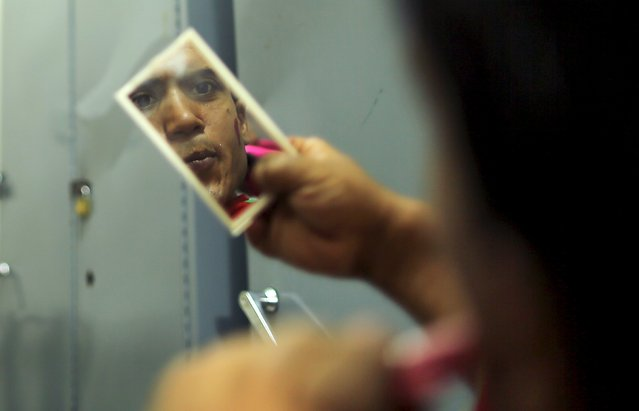 A Palestinian social activist working for the International South South Cooperation (Cooperazione Internazionale Sud Sud, or CISS) looks in a mirror to prepare himself before entertaining children who are cancer patients, inside a hospital in Gaza City August 31, 2015. (Photo by Mohammed Salem/Reuters)