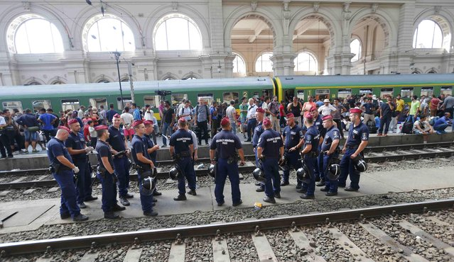 Hungarian policemen stand in front of migrants on a platform at the Keleti train station in Budapest, Hungary, September 3, 2015 as Hungarian police withdrew from the gates after two days of blocking their entry. (Photo by Laszlo Balogh/Reuters)