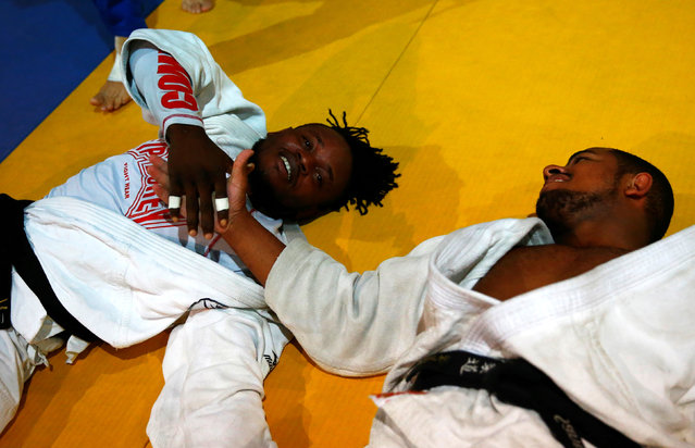 2016 Rio Olympics, Judo, Refugee Olympic Team Training, Reacao Institute, Rio De Janeiro, Brazil on July 29, 2016. Refugee and judo athlete from the Democratic Republic of Congo Popole Misenga (L) shakes hands with his mate from Brazil during a training session. (Photo by Nacho Doce/Reuters)