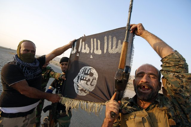Iraqi Shiite militia fighters hold the Islamic State flag as they celebrate after breaking the siege of Amerli by Islamic State militants, September 1, 2014. (Photo by Youssef Boudlal/Reuters)