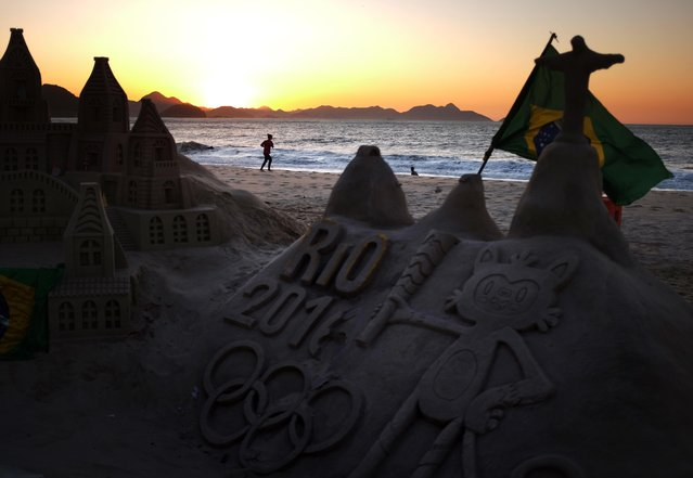 A jogger runs along Copacabana beach as a sand sculpture stands along the promenade Monday, August 1, 2016, in Rio de Janeiro, Brazil. The iconic Copacabana beach will be the starting point for the road cycling race, marathon swimming and triathlon competitions during the Olympics. (Photo by David Goldman/AP Photo)