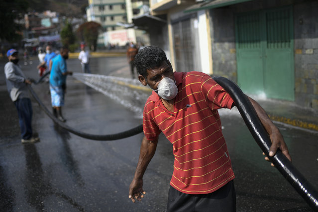"""A man holds a hose during a cleaning and disinfection day organized by the Integral Defense Organization, communal council and pro-government groups known as """"Colectivos"""" at the 23 de Enero neighborhood of Caracas, Venezuela, Wednesday, April 29, 2020, during a government-imposed quarantine to help stop the spread of the new coronavirus. (Photo by Matias Delacroix/AP Photo)"""