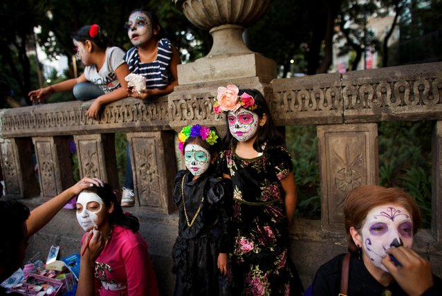 """People have their faces painted in the style of Mexico's iconic """"Catrina"""", as they prepare to march in the Grand Procession of the Catrinas, part of upcoming Day of the Dead celebrations in Mexico City, Sunday, October 22, 2017. The figure of a skeleton wearing an elegant broad-brimmed hat was first done as a satirical engraving by artist Jose Guadalupe Posada sometime between 1910 and his death in 1913. (Photo by Rebecca Blackwell/AP Photo)"""