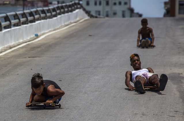 """Boys race down a slope using makeshift carts know as """"chivichanas"""" in downtown Havana, Cuba, Tuesday, July 26, 2016. Cuba marks the anniversary of the July 26, 1953 rebel attack led by Fidel and Raul Castro on the Moncada military barracks. The attack is considered the beginning of the revolution that culminated with dictator Fulgencio Batista's ouster. (Photo by Desmond Boylan/AP Photo)"""