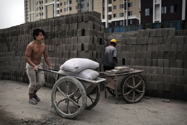 A Chinese construction worker pushes a load of concrete mix at the building site of a new apartment complex on August 29, 2014 in Beijing, China. (Photo by Kevin Frayer/Getty Images)