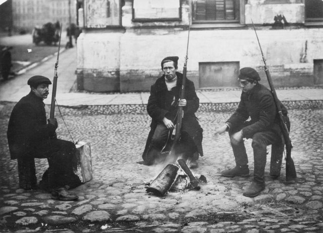 In this photo taken in October 1917, provided by Russian State Archive of Social and Political History, armed revolution workers warm themselves at a bonfire in St.Petersburg, Russia. From left: Ivanov, Yarosh and Gribovsky. The 1917 Bolshevik Revolution was long before the digital revolution allowed anyone to instantly document events. But the clumsy cameras of the time still caught some images that capture the period's drama. (Photo by Yakov Steinberg/Russian State Archive of Social and Political History via AP Photo)