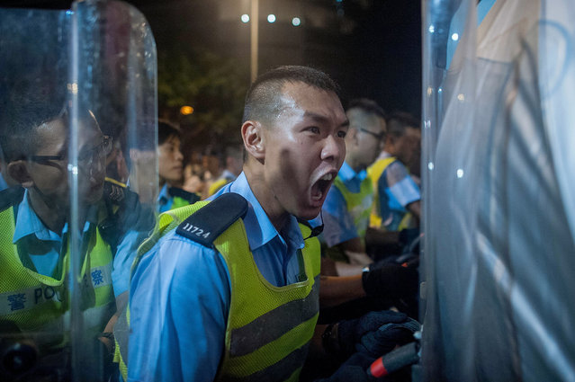 A police officer reacts outside of Hong Kong government complex on September 27, 2014 in Hong Kong. Thousands of students from more than 20 tertiary institutions started a week-long boycott of classes in protest against Beijing's conservative framework for political reform in Hong Kong. (Photo by Anthony Kwan/Getty Images)