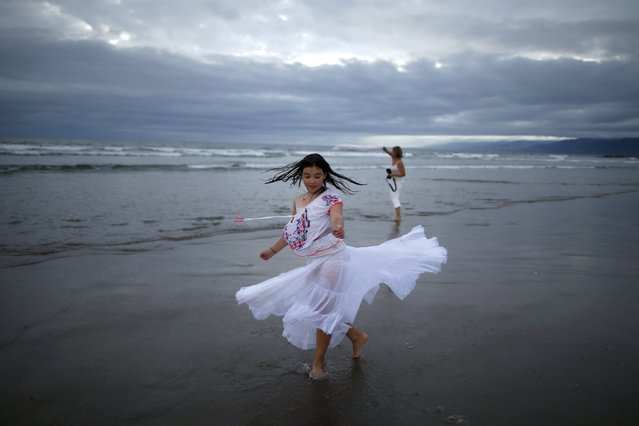 Mira Saville, 11, spins in her petticoat on the sand at the Nashuva Spiritual Community Jewish New Year celebration on Venice Beach in Los Angeles, California, United States September 14, 2015. (Photo by Lucy Nicholson/Reuters)