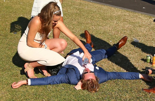 A racegoer is given some water as he lays on the ground following 2017 Stakes Day at Flemington Racecourse on November 11, 2017 in Melbourne, Australia. (Photo by Scott Barbour/Getty Images)