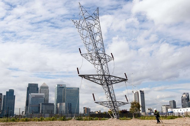 "A workman smooths out the gravel near the base of British artist Alex Chinneck' latest sculpture ""A bullet from a shooting star"" on the Greenwich Peninsula in London on September 17, 2015. The 35-metre tall, upside-down electricity pylon overlooks the Canary Wharf financial district. (Photo by Leon Neal/AFP Photo)"