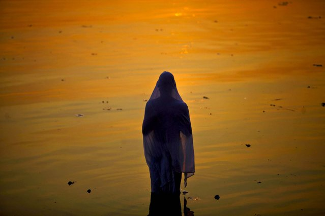 A Hindu devotee performs rituals at sunset during Chhath Puja festival, in Hyderabad, India, November 19, 2012. On Chhath, an ancient Hindu festival, rituals are performed to thank the Sun God for sustaining life on earth. (Photo by Mahesh Kumar/Associated Press)