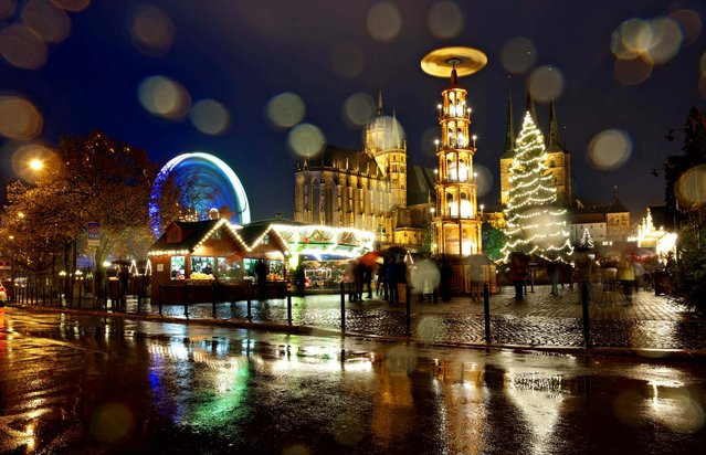 Booths offer traditional Thuringian handcrafts and sweets and a big Ferris wheel stand at the Christmas Fair in front of the Cathedral of Mary, center left,  and St. Severi's Church, right, in Erfurt, Germany. (Photo by Jens Meyer/Associated Press)