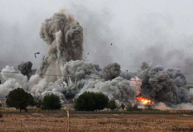 In this Sunday, October 12, 2014 file photo, thick smoke, debris and fire rise following an airstrike by the US-led coalition in Kobani, Syria as fighting intensified between Syrian Kurds and the militants of Islamic State group, as seen from Mursitpinar on the outskirts of Suruc, at the Turkey-Syria border. (Photo by Lefteris Pitarakis/AP Photo)