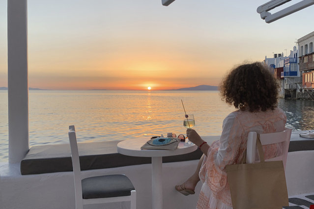 In this Tuesday, June 9, 2020 photo, a visitor watches the sunset at a bar in an area known as Little Venice in the main town of the island of Mykonos, Greece. Business owners and locals officials on the Greek holiday island of Mykonos, a popular vacation spot for celebrities, club-goers, and high rollers, say they are keen to reopen for business despite the risks of COVID-19 posed by international travel. Greece will official launch its tourism season Monday, June 15, 2020 after keeping the country's infection rate low. (Photo by Derek Gatopoulos/AP Photo)