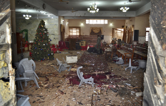 A Pakistani walks in the main hall of a church following a suicide attack in Quetta, Pakistan, Sunday, December 17, 2017. Two suicide bombers attacked the church when hundreds of worshippers were attending services at the church ahead of Christmas. (Photo by Arshad Butt/AP Photo)