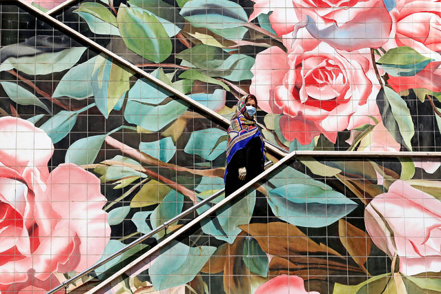 An Iranian woman wearing a protective mask due to the COVID-19 pandemic, climbs up a decorated stairway in the capital Tehran, on July 14, 2020. (Photo by Atta Kenare/AFP Photo)