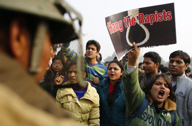 An Indian demonstrator (2nd R) shouts slogans at the police during a protest calling for  better safety for women following the rape of a student last week, in front the India Gate monument in New Delhi on December 23, 2012. In the biggest protest so far, several thousand college students rallied at the India Gate monument in the heart of the capital where they were baton-charged, water cannoned and tear gassed by the police. (Photo by Andrew Caballero-Reynolds/AFP Photo)