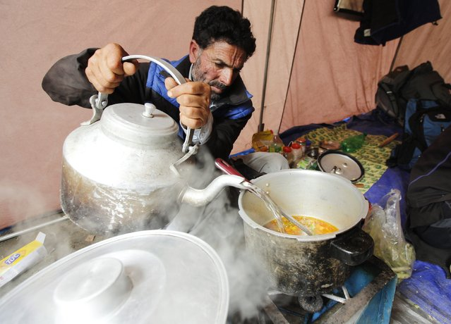 Shukrullah Baig, a 52-year-old brick layer and former cook at a five-star hotel chain cooks Vegetable Masala on his kerosene burner in the village of Askole in the Karakoram mountain range in northern Pakistan September 11, 2014. (Photo by Wolfgang Rattay/Reuters)
