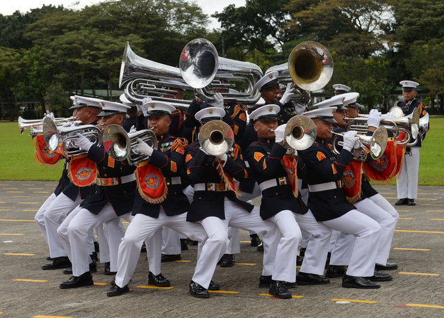 """Members of the Philippines' military brass band perform during a ceremony marking the anniversary of the military at Camp Aguinaldo in Quezon City, suburban Manila on December 20, 2017, attended by President Rodrigo Duterte. President Duterte has ordered the military to suspend operations against communist rebels over Christmas, the government said December 20, despite ending peace talks and branding the insurgents """"terrorists"""". (Photo by  Ted Aljibe/AFP Photo)"""