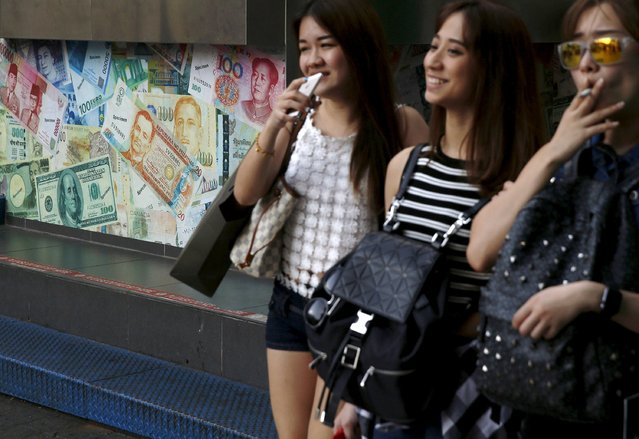 Women walk past a money changer in the central shopping district in Kuala Lumpur, Malaysia, August 21, 2015. (Photo by Olivia Harris/Reuters)