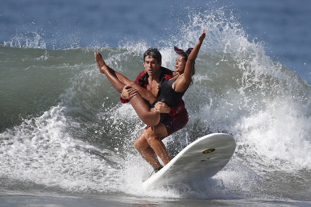 Jeremy Porfilio, 41, and Tammy Mowery ride a wave dressed as Playboy founder Hugh Hefner and his ex-girlfriend Kendra Wilkinson during the 7th annual ZJ Boarding House Haunted Heats Halloween surf contest in Santa Monica, October 25, 2014. (Photo by Lucy Nicholson/Reuters)