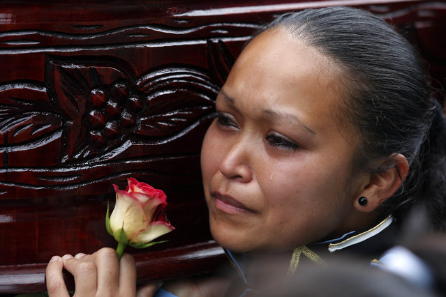 A student, member of the school marching band cries as she carries the coffin of her classmate and fellow band member Bryan Sandoval who died in a mudslide, to the Santa Catarina Pinula cemetery on the outskirts of Guatemala City, Sunday, October 4, 2015. (Photo by Moises Castillo/AP Photo)