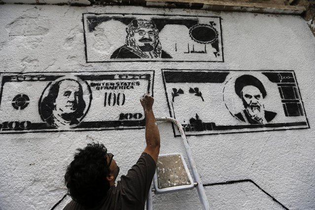 Artist and activist Murad Subai puts final touches on his graffiti depicting Saudi, U.S. and Iranian currency banknotes on a wall, during a graffiti campaign against foreign interference in the internal affairs of Yemen, in Sanaa May 15, 2014. (Photo by Khaled Abdullah/Reuters)