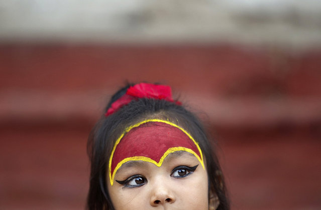 A young Nepalese girl wearing traditional attire waits for the Kumari puja to start at Hanuman Dhoka temple, in Kathmandu, Nepal, Wednesday, September 14, 2016. (Photo by Niranjan Shrestha/AP Photo)