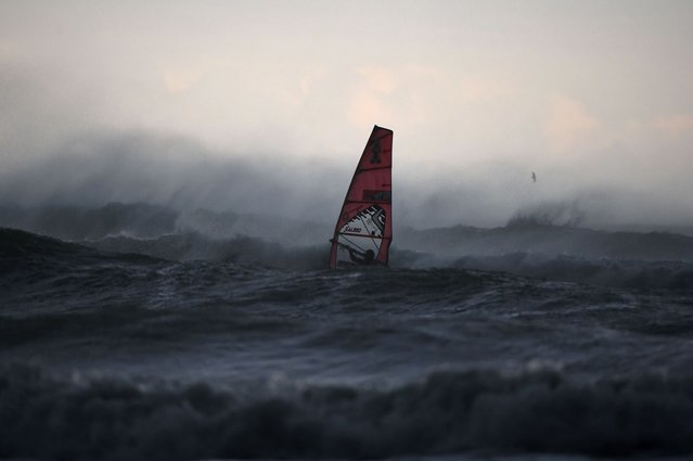 A windsurfer rides on the northern coast of Italy in Aurelia (western Genova) on November 4, 2014 in Andora. (Photo by Olivier Morin/AFP Photo)